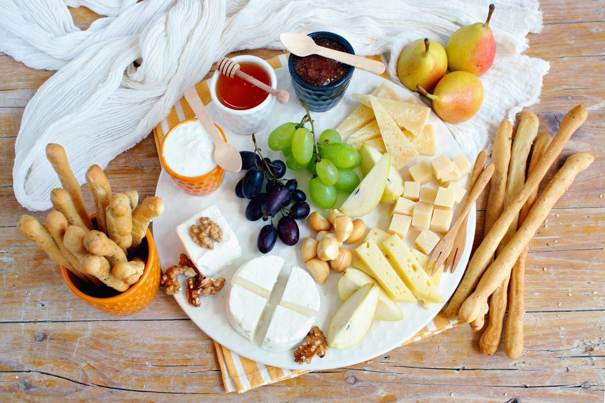 Antipasto di grissini con formaggi, frutta, miele e confettura